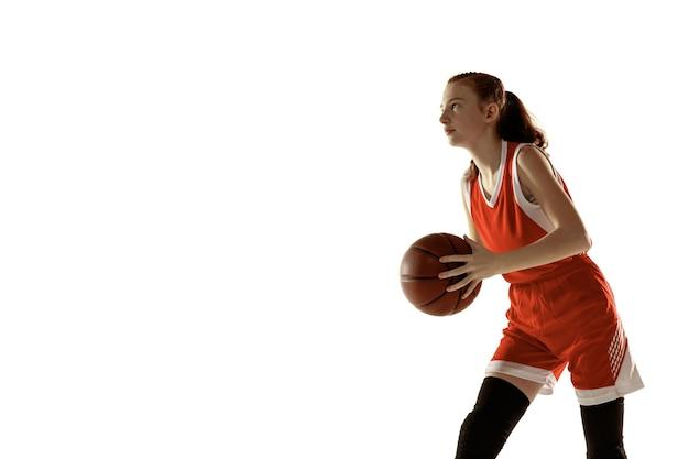 動作中の若い白人女性バスケットボール選手、白い背景で隔離の実行中の動き。赤毛のスポーティーな女の子。スポーツ、運動、エネルギー、ダイナミックで健康的なライフスタイルのコンセプト。トレーニング。