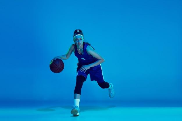 네온 불빛에 파란색 스튜디오 배경에 고립 된 젊은 백인 여성 농구 선수