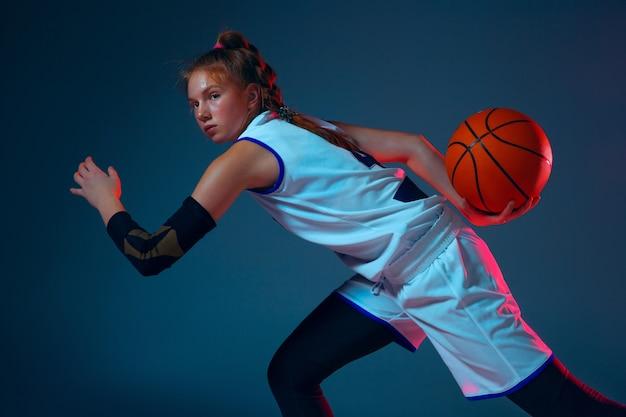 ネオンの光の青い壁に若い白人女性バスケットボール選手