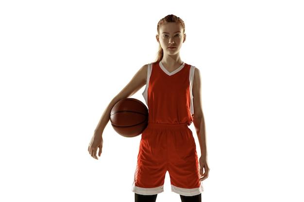 白い背景で隔離の自信を持ってポーズをとる若い白人女性バスケットボール選手。赤毛のスポーティーな女の子。スポーツ、運動、エネルギー、ダイナミックで健康的なライフスタイルのコンセプト。トレーニング、練習。