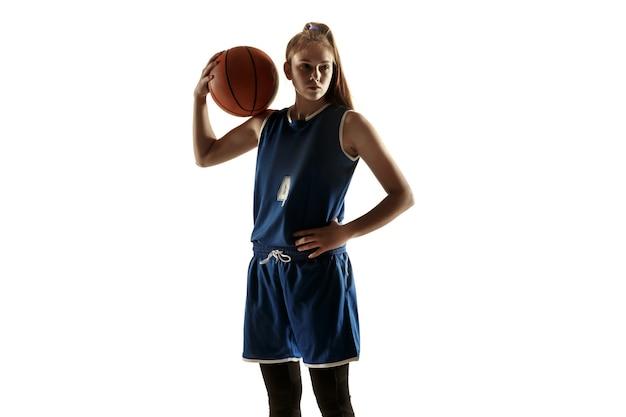 Giovane giocatore di pallacanestro femminile caucasico della squadra che posa fiducioso con la sfera isolata su fondo bianco.