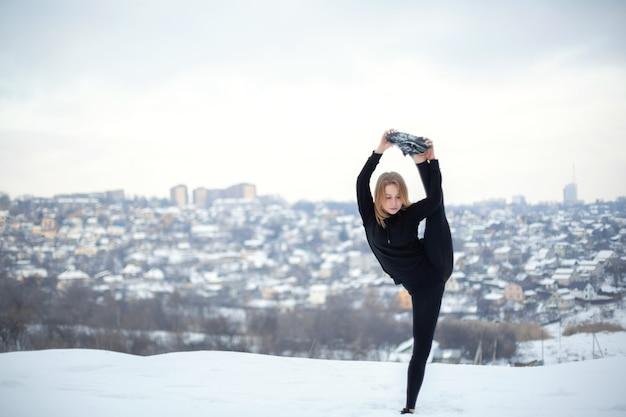 雪に覆われた森の野外で運動を伸ばすレギンスの若い白人女性ブロンド