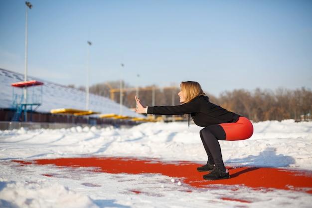 Молодая кавказская блондинка в фиолетовых леггинсах, растягивая упражнение на красной беговой дорожке на заснеженном стадионе. фитнес и спортивный образ жизни