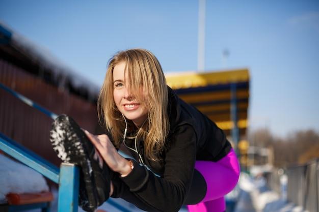 Молодая кавказская блондинка в фиолетовых леггинсах, растягивая упражнение на трибуне на заснеженном стадионе. подтянутый и спортивный образ жизни.