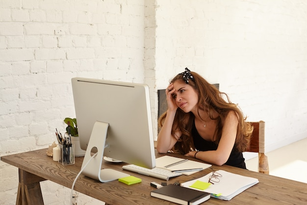 Young caucasian female designer feels panic from the coming deadline for her work, sitting at workplace with papers, notepad and looks in the computer monitor against white brick wall, looking puzzled