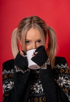 앉아 차를 마시는 귀여운 스웨터에 젊은 백인 여성