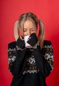 차를 마시는 귀여운 스웨터에 젊은 백인 여성