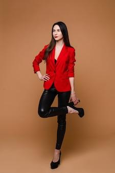 Молодая кавказская модель с длинными темными прямыми волосами в красной куртке, черных кожаных брюках и черных туфлях