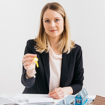 Young caucasian female real estate agent holding key looking at camera