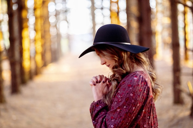 Young caucasian female in a stylish black hat praying in the scenic forest, autumn mood