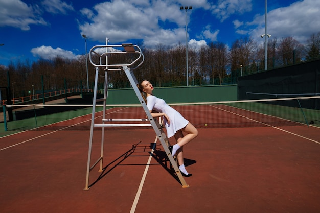 Young caucasian female tennis player on the court stays near the referee's ladder
