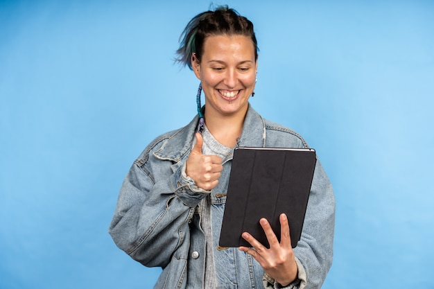Young caucasian female on video call and showing approval gesture on the tablet on a blue wall