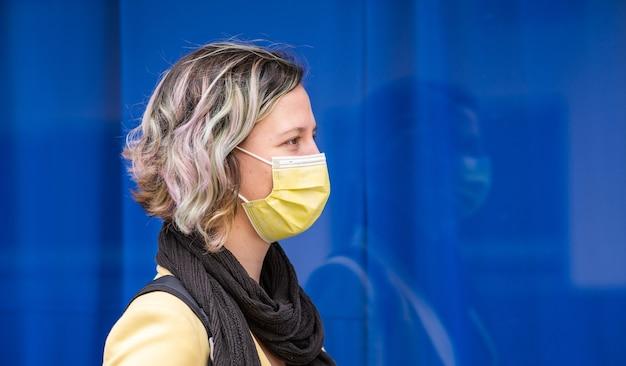 파란 벽에 서 있는 마스크를 쓴 젊은 백인 여성