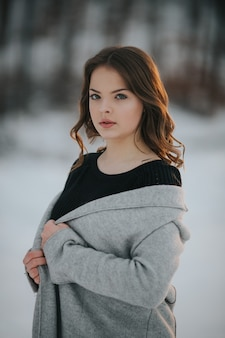Young caucasian female wearing a gray coat posing in a winter park covered in snow