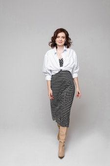 黒と白の長い夏のドレスと白いシャツと笑顔の短い栗のウェーブのかかった髪の若い白人女性