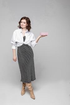 黒と白の長い夏のドレスと白いシャツの短い栗のウェーブのかかった髪の若い白人女性は、イヤリングのペアを保持します