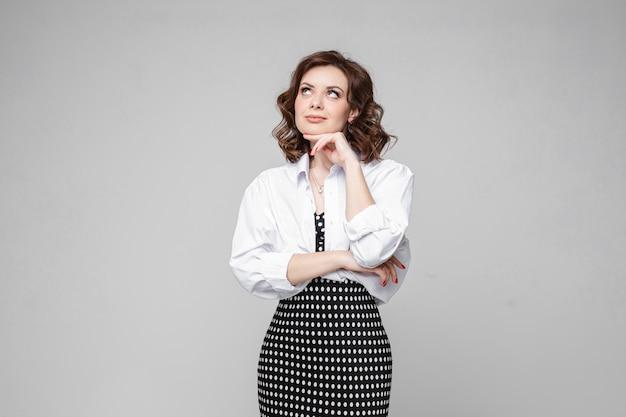 黒と白の長い夏のドレスと白いシャツの短い栗のウェーブのかかった髪を持つ若い白人女性は何かを考えて笑顔