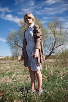 晴れた日にフィールドに立っている斑点のあるドレスとセーターの短い髪の若い白人女性
