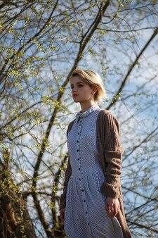 斑点のあるドレスと木の前に立っているセーターの短い髪の若い白人女性