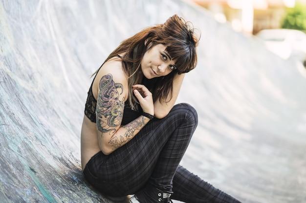Молодая кавказская женщина с татуировками сидит на рампе для катания на коньках