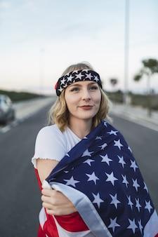 그녀의 어깨에 미국 국기와 함께 젊은 백인 여성