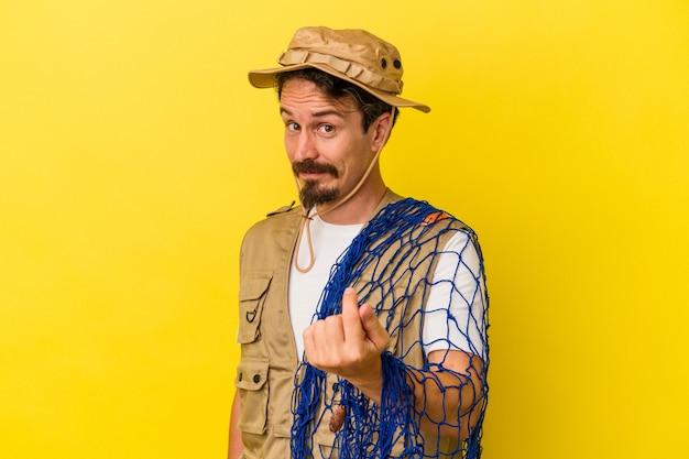 黄色の背景で隔離されたネットを持っている若い白人の漁師は、招待が近づくようにあなたに指を指しています。