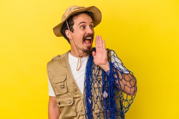 黄色の背景で隔離のネットを保持している若い白人漁師は、開いた口の近くで叫び、手のひらを保持しています。
