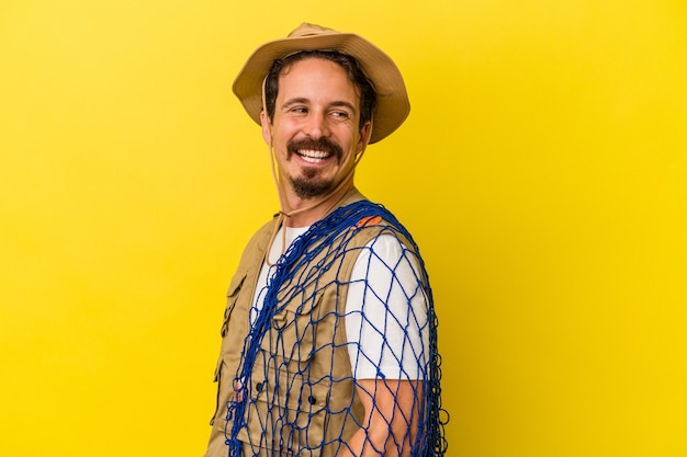Young caucasian fisherman holding net isolated on yellow background looks aside smiling, cheerful and pleasant.