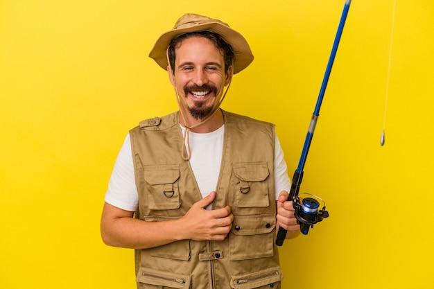 Молодой кавказский рыбак, держащий стержень, изолированный на желтом фоне, смеясь и весело.
