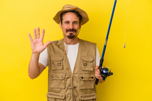 Young caucasian fisherman holding rod isolated on yellow background smiling cheerful showing number five with fingers.
