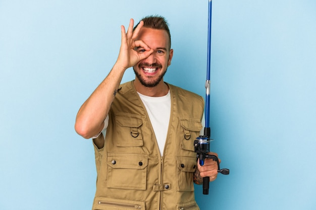 Young caucasian fisherman with tattoos holding rod isolated on blue background  excited keeping ok gesture on eye.