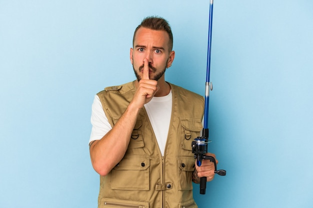 Young caucasian fisherman with tattoos holding rod isolated on blue background  keeping a secret or asking for silence.