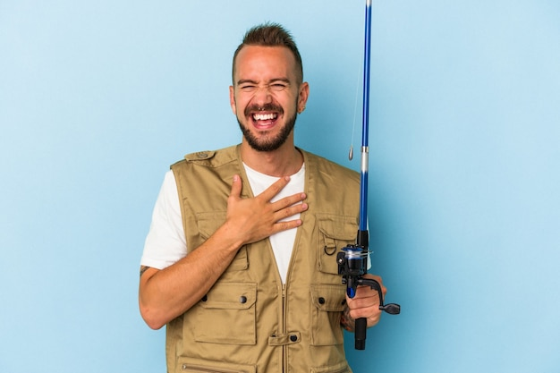 Young caucasian fisherman with tattoos holding rod isolated on blue background  laughs out loudly keeping hand on chest.