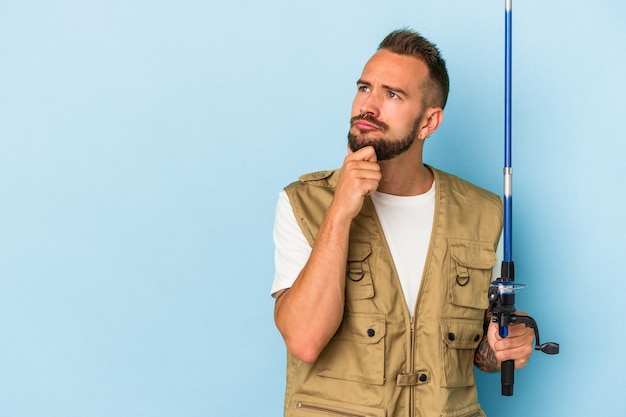 Young caucasian fisherman with tattoos holding rod isolated on blue background  looking sideways with doubtful and skeptical expression.