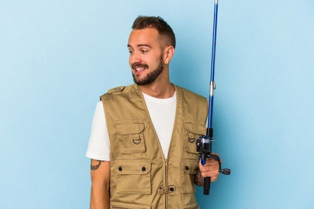 Young caucasian fisherman with tattoos holding rod isolated on blue background  looks aside smiling, cheerful and pleasant.