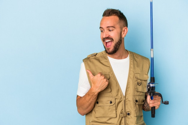 Young caucasian fisherman with tattoos holding rod isolated on blue background  points with thumb finger away, laughing and carefree.