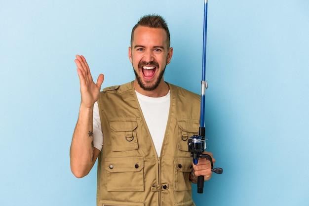 Young caucasian fisherman with tattoos holding rod isolated on blue background  receiving a pleasant surprise, excited and raising hands.