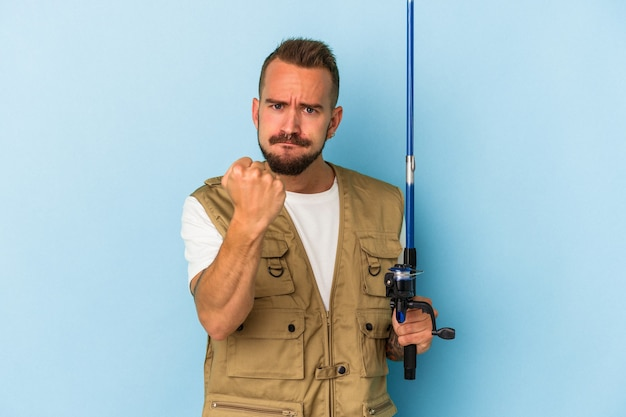 Young caucasian fisherman with tattoos holding rod isolated on blue background  showing fist to camera, aggressive facial expression.