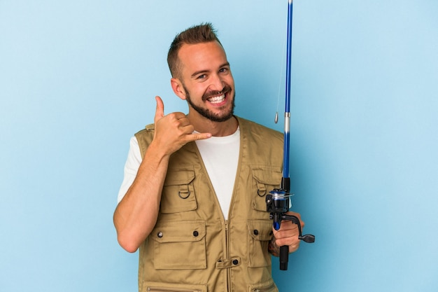 Young caucasian fisherman with tattoos holding rod isolated on blue background  showing a mobile phone call gesture with fingers.