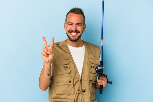 Young caucasian fisherman with tattoos holding rod isolated on blue background  showing number two with fingers.