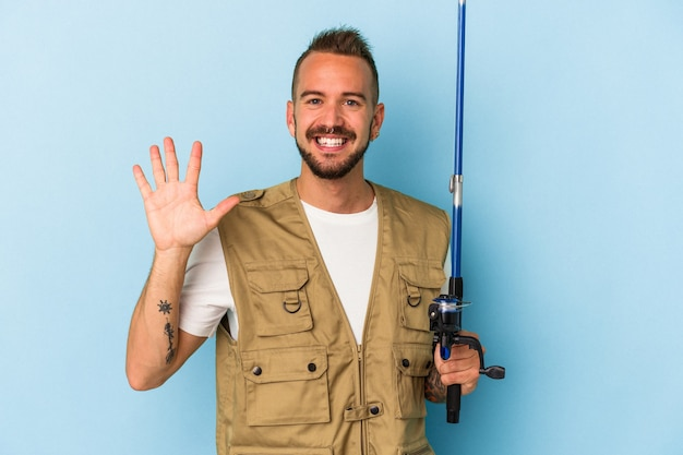 Young caucasian fisherman with tattoos holding rod isolated on blue background  smiling cheerful showing number five with fingers.