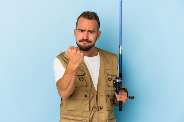 カメラに拳、攻撃的な表情を示す青い背景に分離されたロッドを保持している入れ墨を持つ若い白人漁師。