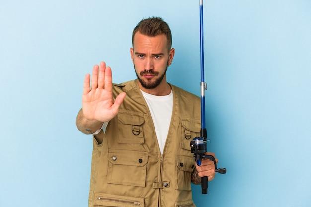 一時停止の標識を示す伸ばした手で立っている青い背景に分離されたロッドを保持している入れ墨を持つ若い白人漁師は、あなたを防ぎます。