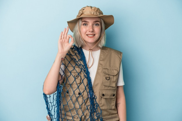 青の背景に隔離されたネットを保持している若い白人の漁師は、陽気で自信を持って大丈夫なジェスチャーを示しています。
