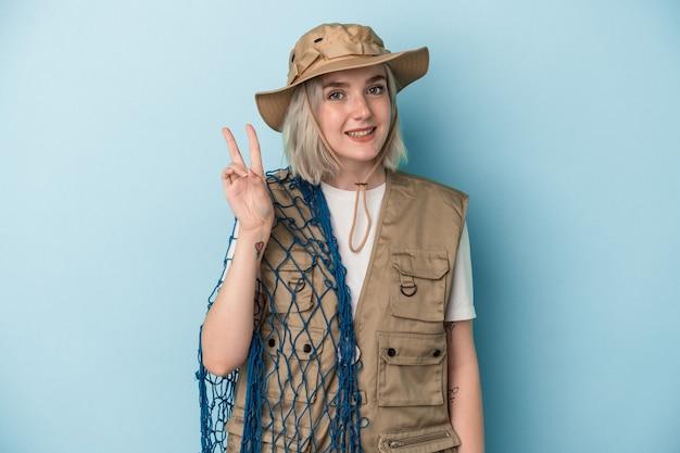 青の背景に隔離されたネットを持っている若い白人の漁師は、指で平和のシンボルを示して楽しくてのんきです。