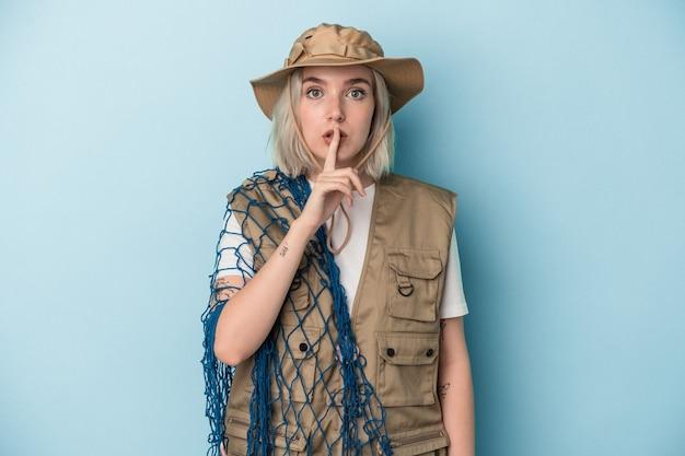 秘密を保持するか、沈黙を求めて青い背景で隔離のネットを保持している若い白人の漁師。