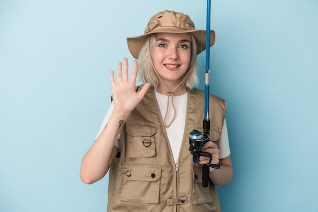 青い背景に分離されたロッドを保持している若い白人の漁師は、指で5番を示して陽気に笑っています。