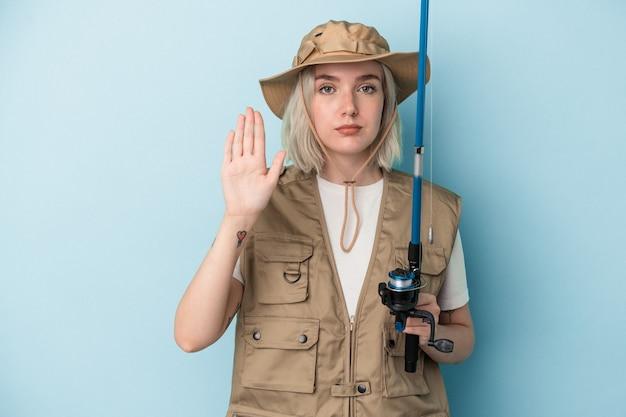 一時停止の標識を示す伸ばした手で立っている青い背景で隔離の棒を保持している若い白人の漁師は、あなたを防ぎます。