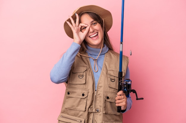 ピンクの背景に分離されたロッドを保持している若い白人の漁師は、目に大丈夫なジェスチャーを維持して興奮しました。