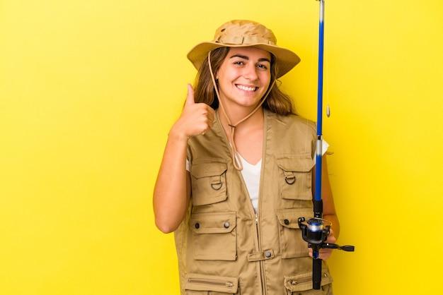Молодая кавказская рыбак, держащая удочку, изолированную на желтом фоне, улыбается и поднимает большой палец вверх